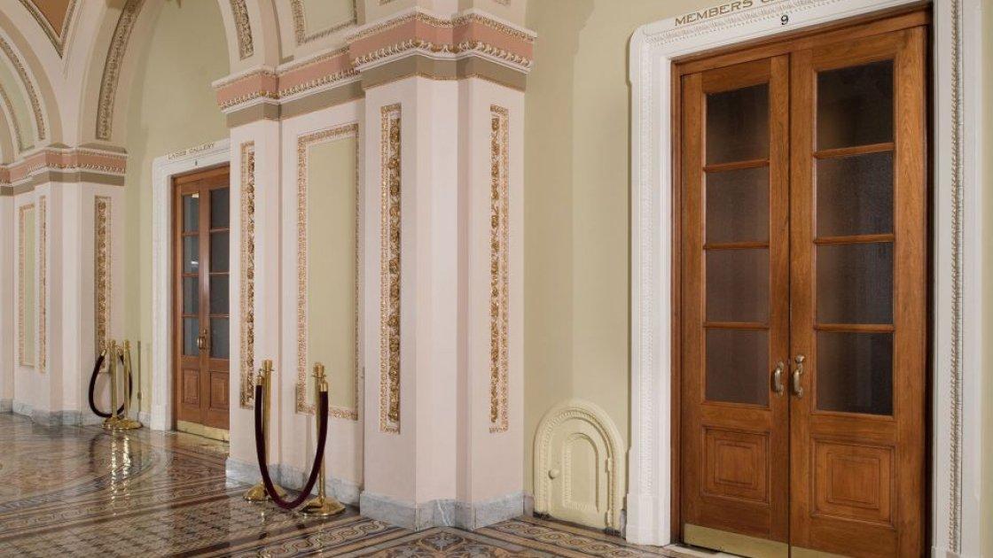 Маленькая дверца в коридоре Капитолия на фоне большой двери