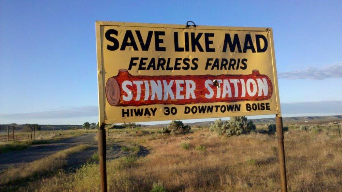 Желтый щит с рекламой Stinker Station